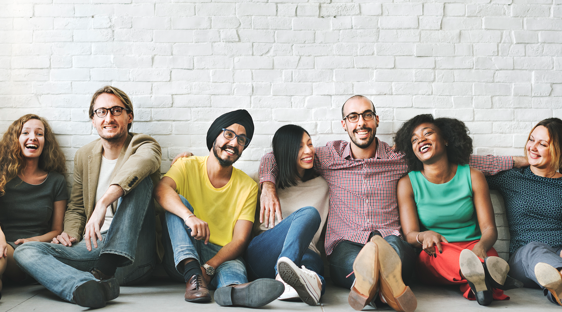 Group of young diverse individuals sitting againts brick wall