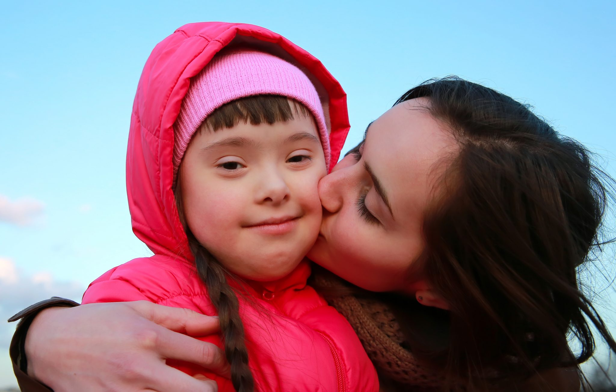 Adult woman embracing and kissing a young child on the cheek.