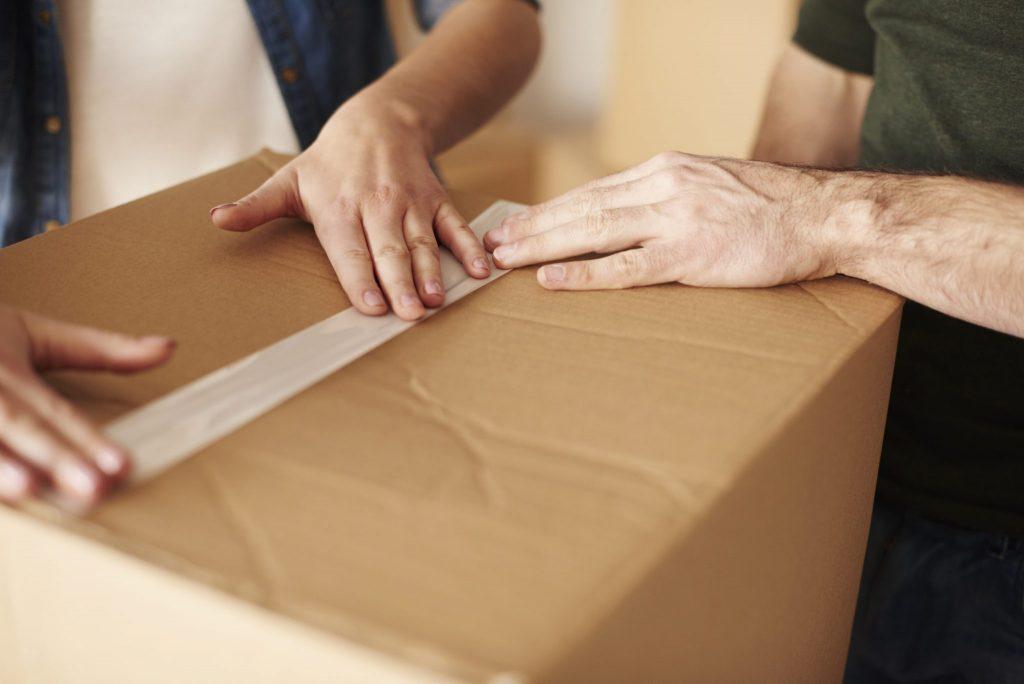 Deux personnes qui ferment une grosse boîte de carton avec du ruban d'emballage adhésif.