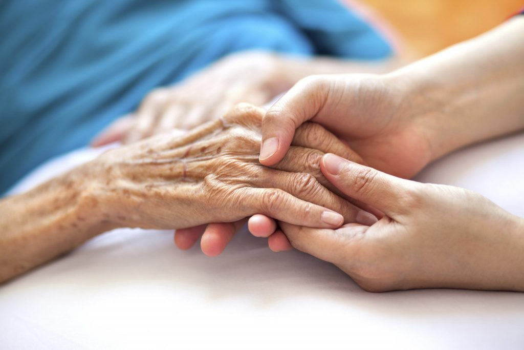 A younger white woman holding an older white woman's hands