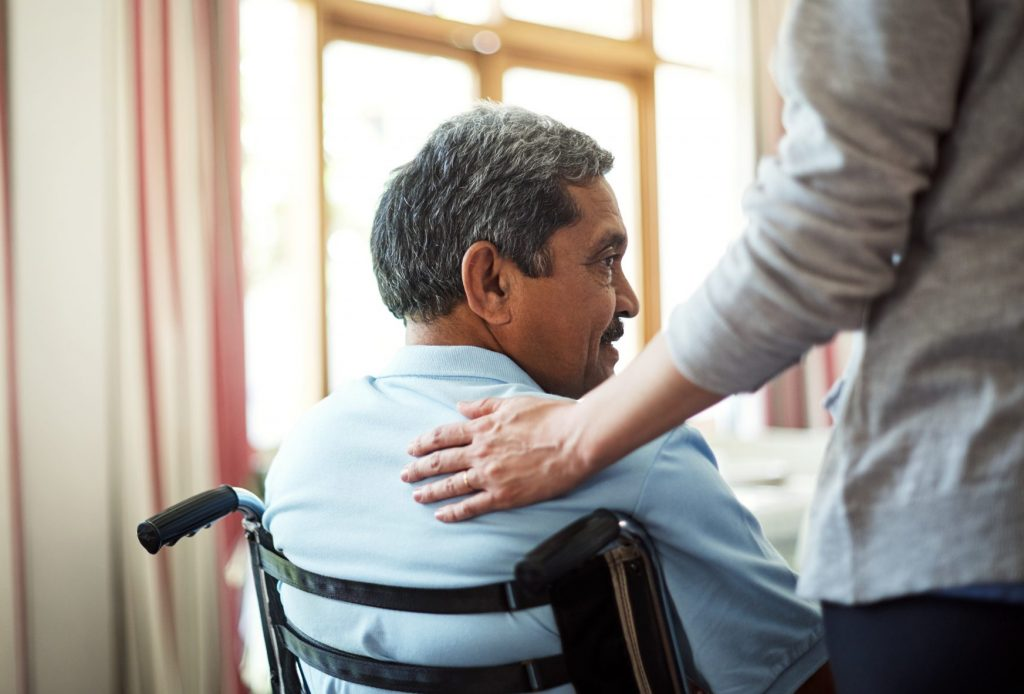 A brown skinned, middle-aged man in a wheelchair being comforted by another person whose hand is on the man's back.
