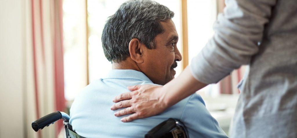 Un homme d'âge moyen à peau brune assis dans un fauteuil roulant se faisant réconforter par une autre personne dont la main est posée sur son dos.