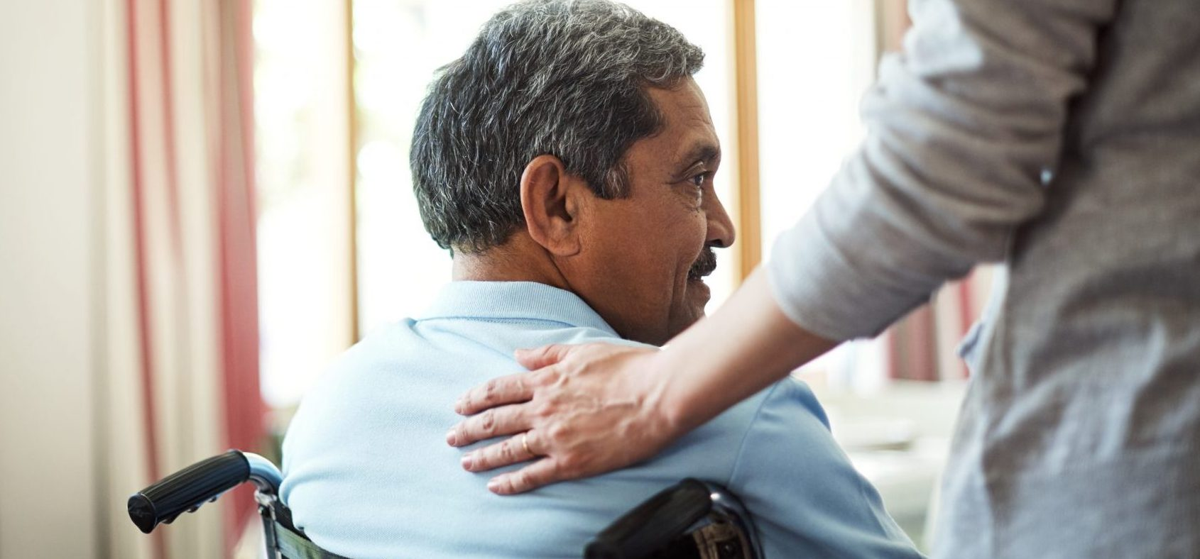 Man in a wheelchair with another person's comforting hand on his shoulder.