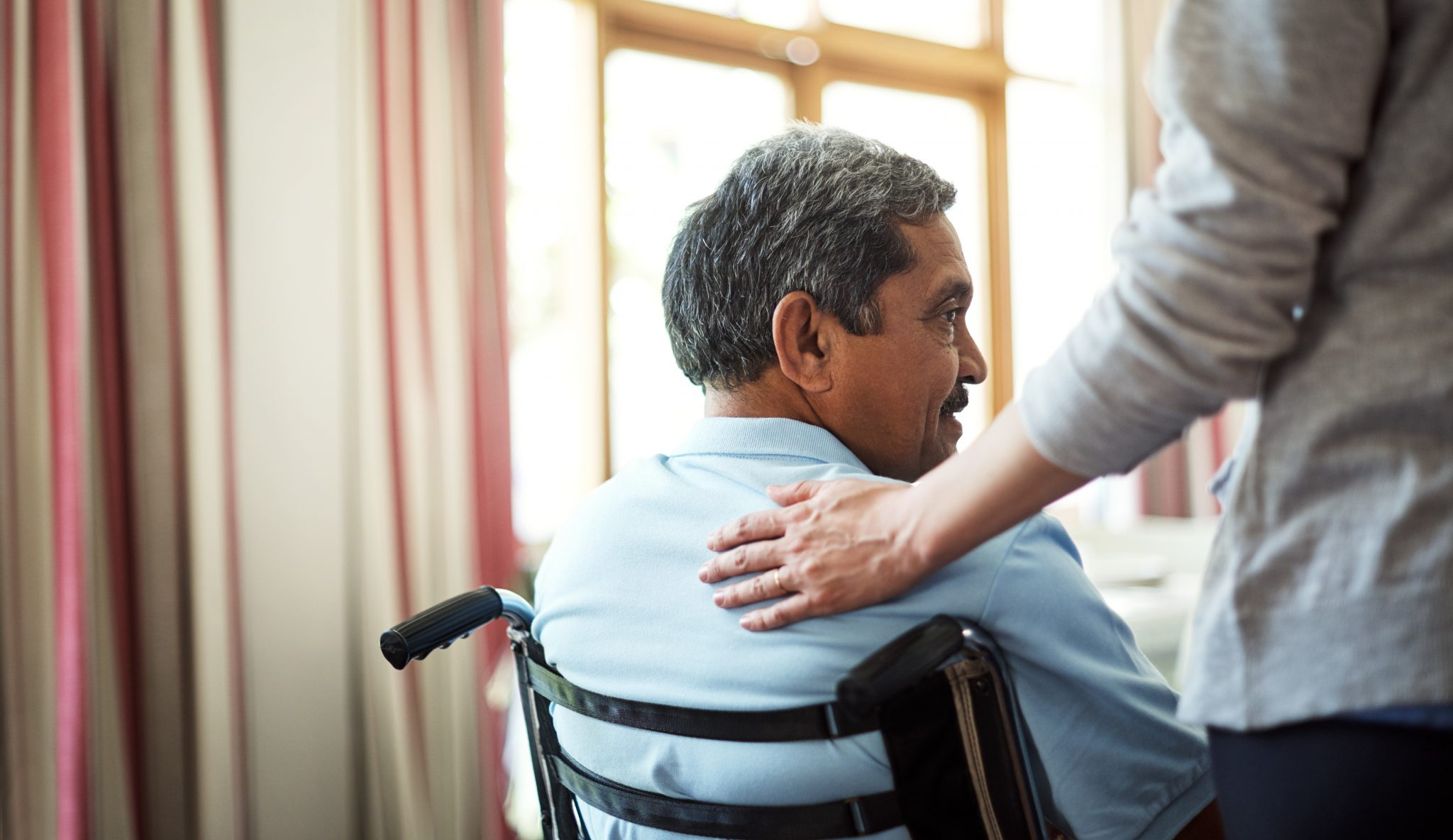 Adult man sitting in a wheelchair with another person's hand gently placed on his shoulder.