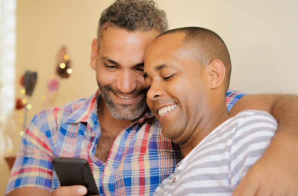 Two middle-aged multi-racial men sitting on a couch looking at a phone