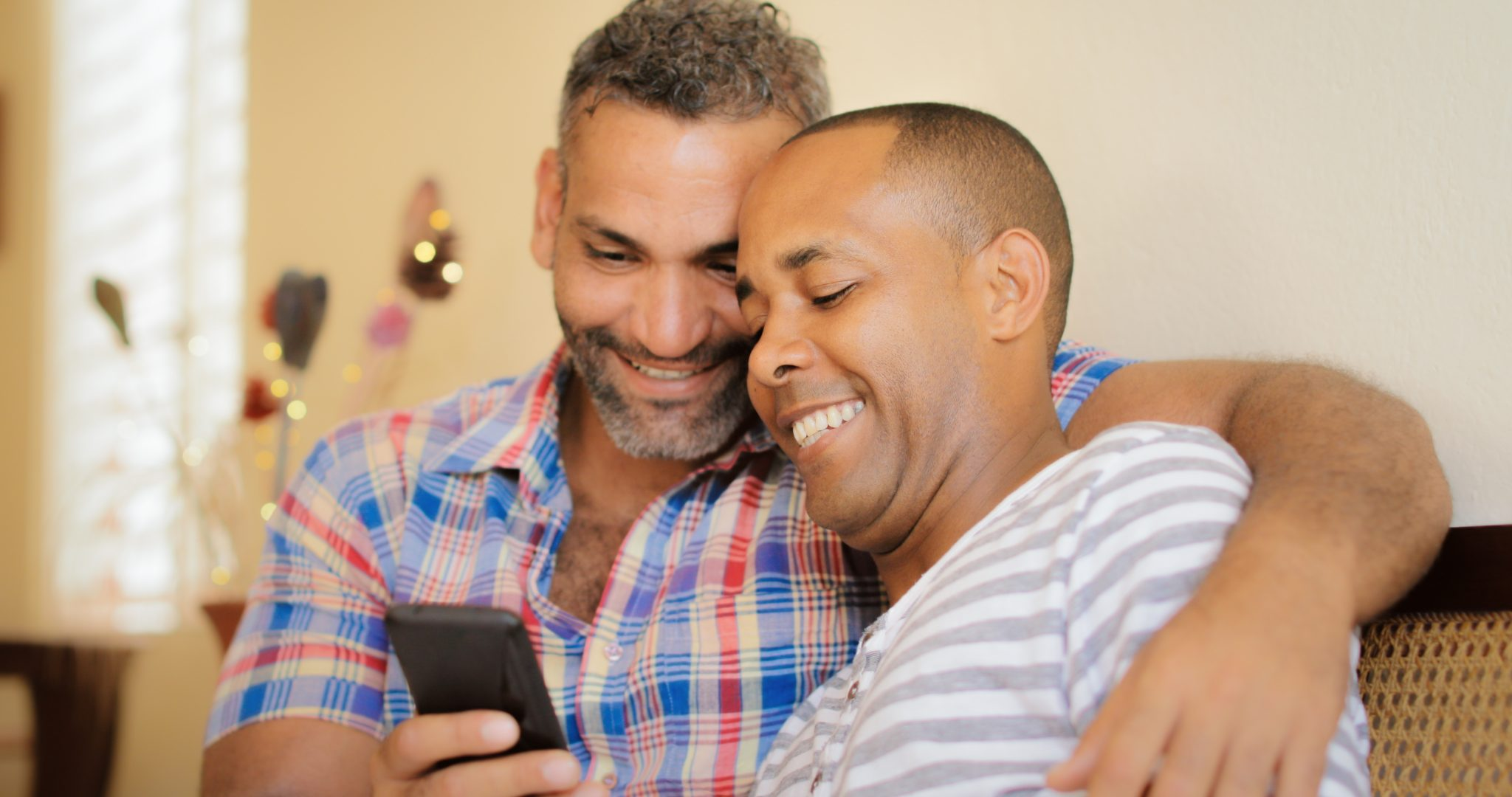 Two smiling men, sitting together in an embrace looking at their cell phone.