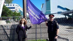 Barb Iacono & Deputy Chief Brad Hill Raising WEAAD Flag