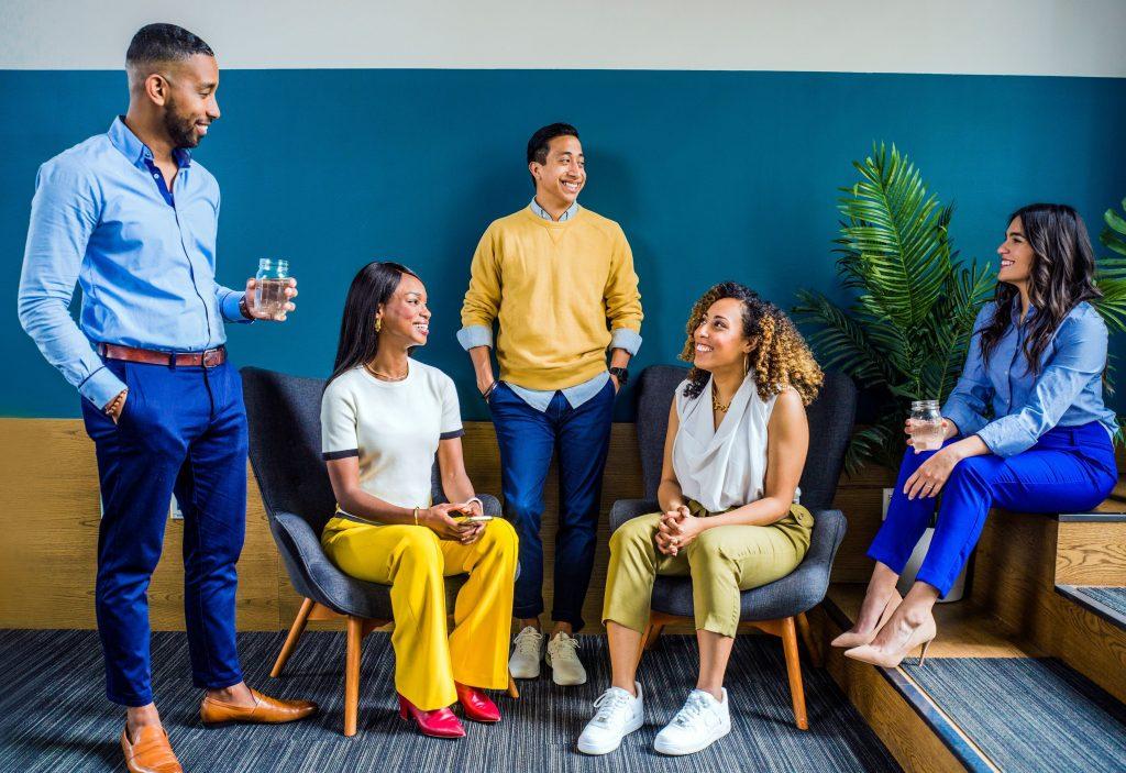 Un groupe de personnes multiraciales dans une pièce dont certaines sont debout et d'autres assises regardant dans différentes directions.
