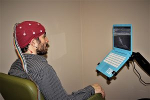 Man sitting down with a red sensor cap on his head for a Brain Mapping Session