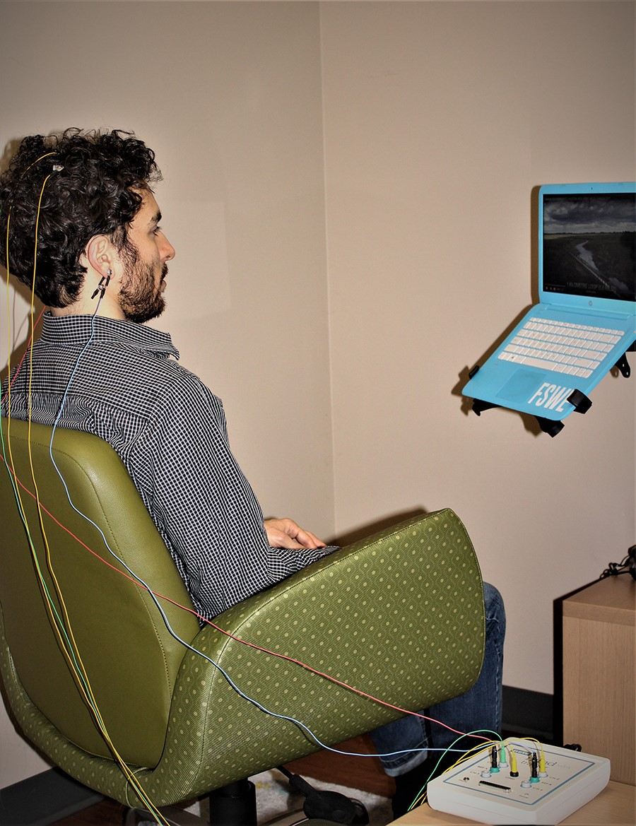 Man sitting in chair with a few sensors attached to his head facing a computer for Brain Training Session