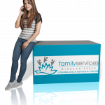 Young woman leaning on box with FSWE logo, talking on the phone