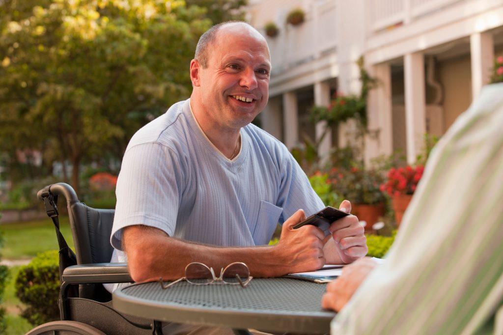 Un homme blanc d'âge moyen souriant assis dans un fauteuil roulant regardant quelqu'un en face de lui à une table.