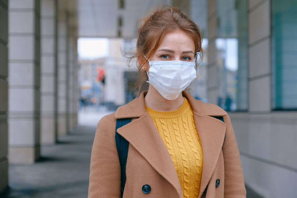 A young white woman wearing a surgical mask standing outside next o a tall concrete building
