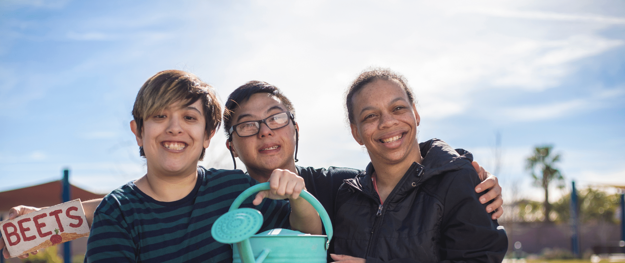 Three, young people from diverse backgrounds smiling