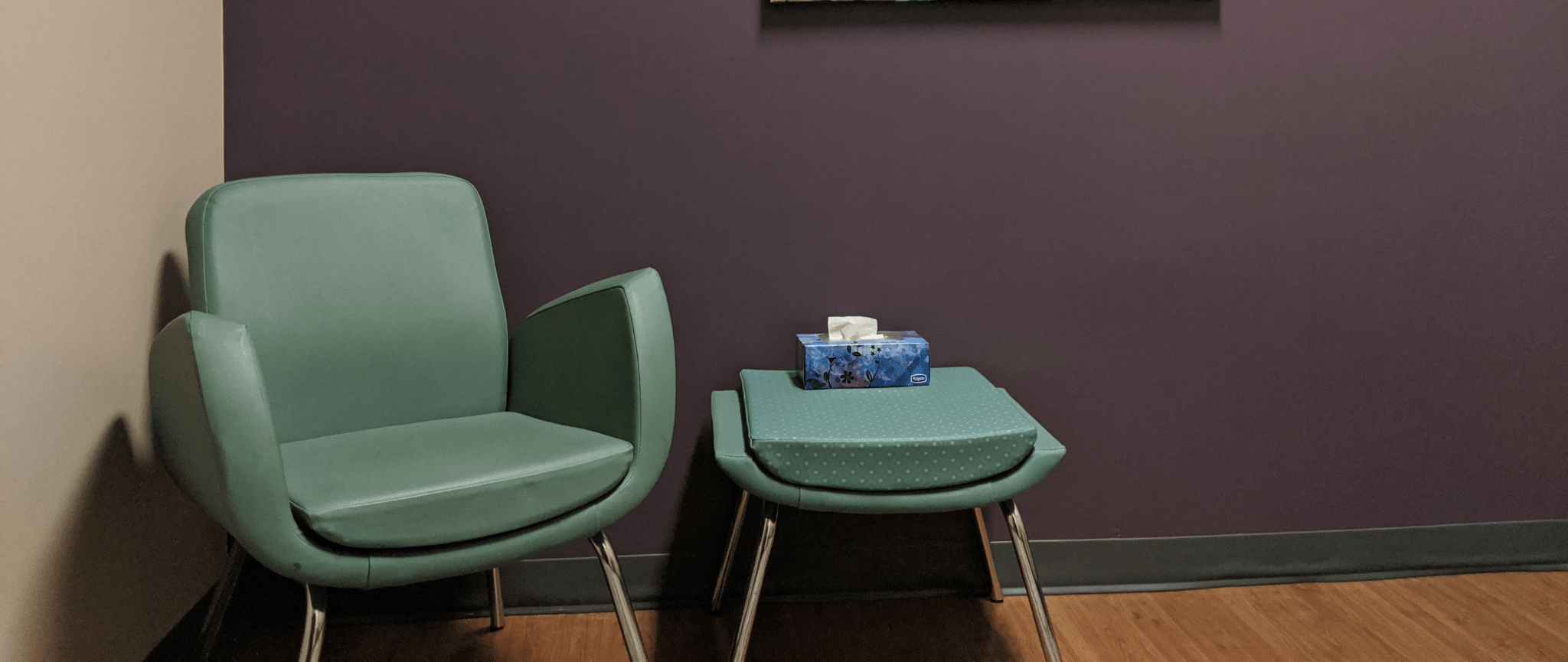 Un fauteuil vert avec un tableau d'une image florale dans un des bureaux des services de counseling de SFWE