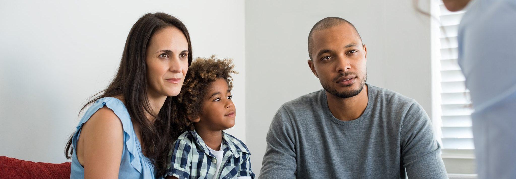 Un couple multiracial composé d'un homme et une femme qui s'entretiennent avec un conseiller pendant qu'un petit garçon est assis sur les genoux de la femme.