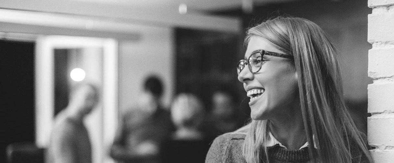 Une femme souriante qui est debout et qui regarde de profil un groupe de personnes derrière elle.