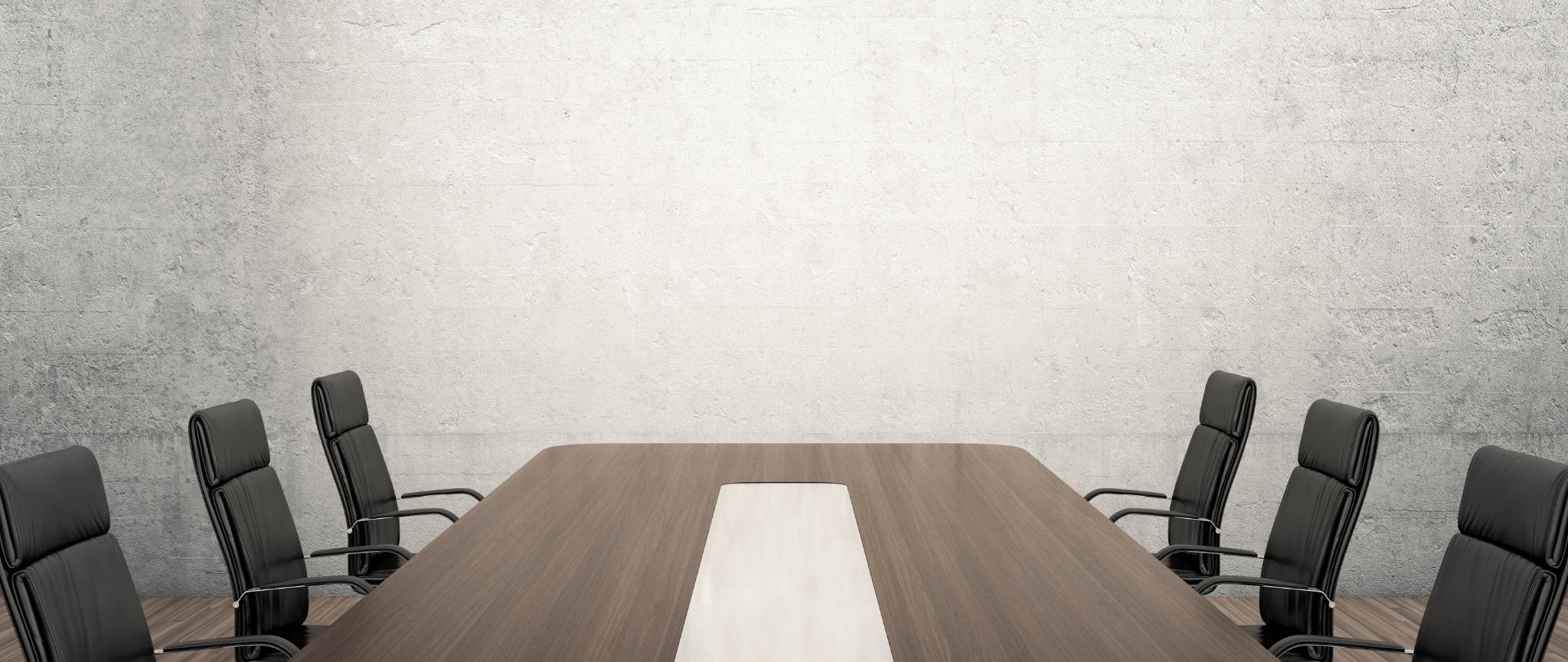 Une salle de rencontre avec une grande table en bois avec six chaises de bureau en cuir noir autour de la table