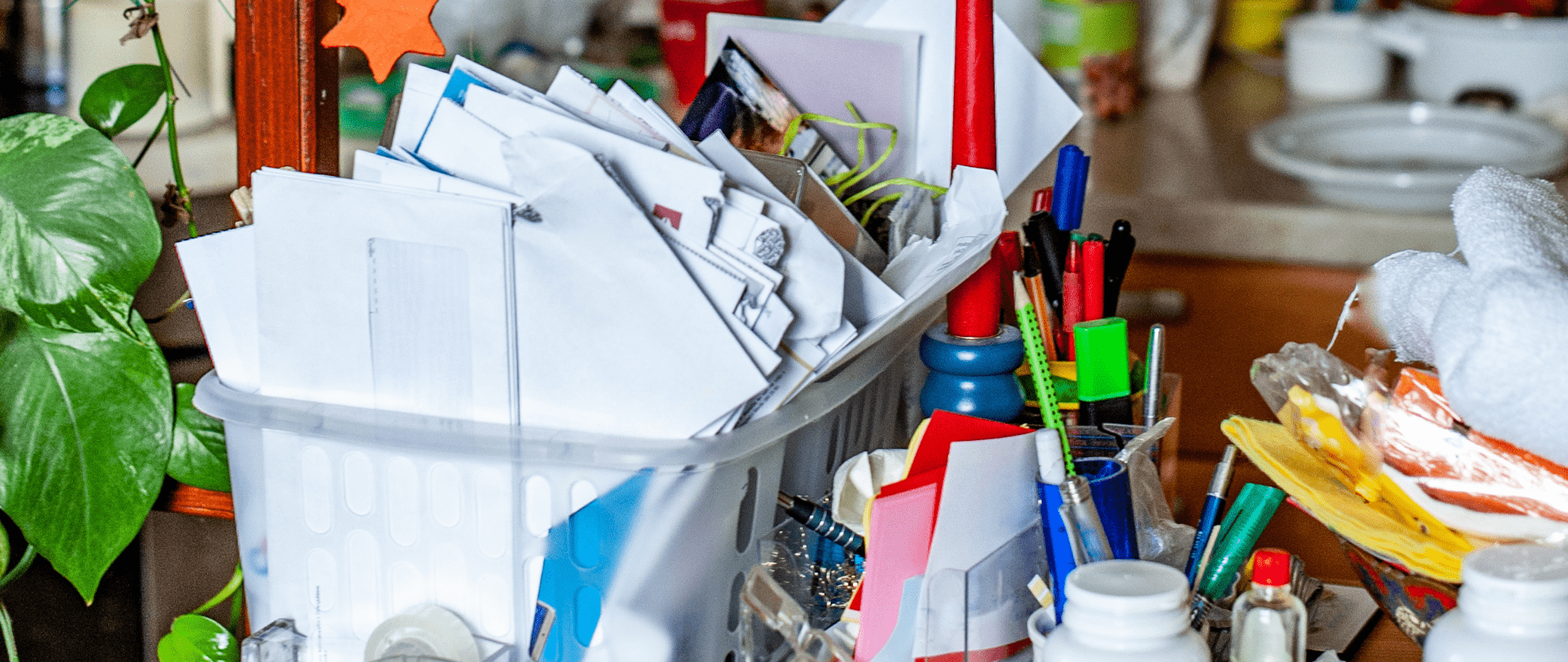 A messy kitchen countertop with a plastic bin overflowing with papers and other objects