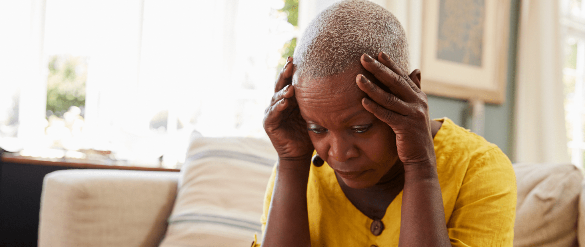 Une personne âgée noire qui a la tête dans les mains et qui a l'air stressée.
